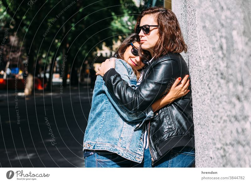 couple of women hugging in the street woman lesbian love female homosexual outdoors girlfriend happy lifestyle affectionate romance togetherness relationship