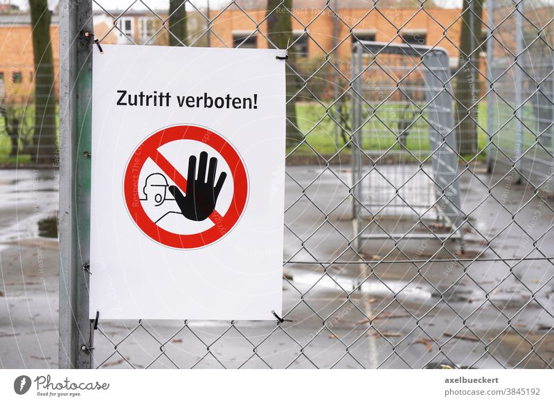 Closed sports ground with prohibition sign Zutritt verboten - meaning no entry in German zutritt verboten closed germany corona fence football soccer closure