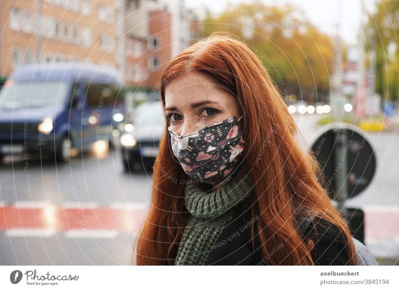 young woman wearing everyday cloth face mask outdoors in city raffic street traffic corona winter air pollution real people everyday mask community mask