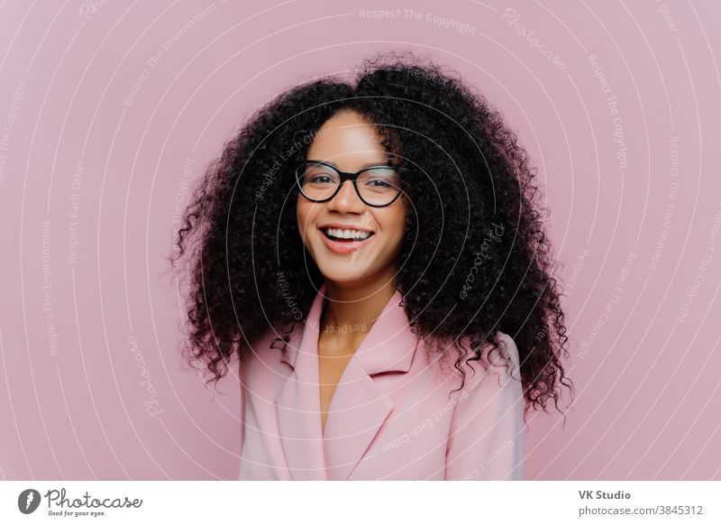 Positive curly haired businesswoman wears spectacles, formal wear, has bushy hairstyle, being in good mood after successful day at work, poses against violet background. Monochrome. Happy director