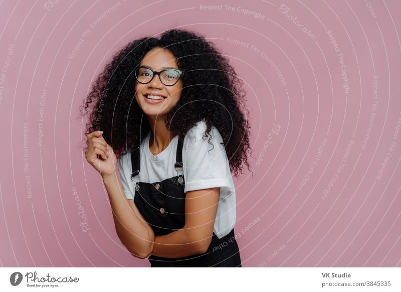 Studio shot of happy dark skinned lady with crisp hair, has dreamy expression, wears optical glasses, stylish clothes, imagines something pleasant, stands against bright violet background, free space