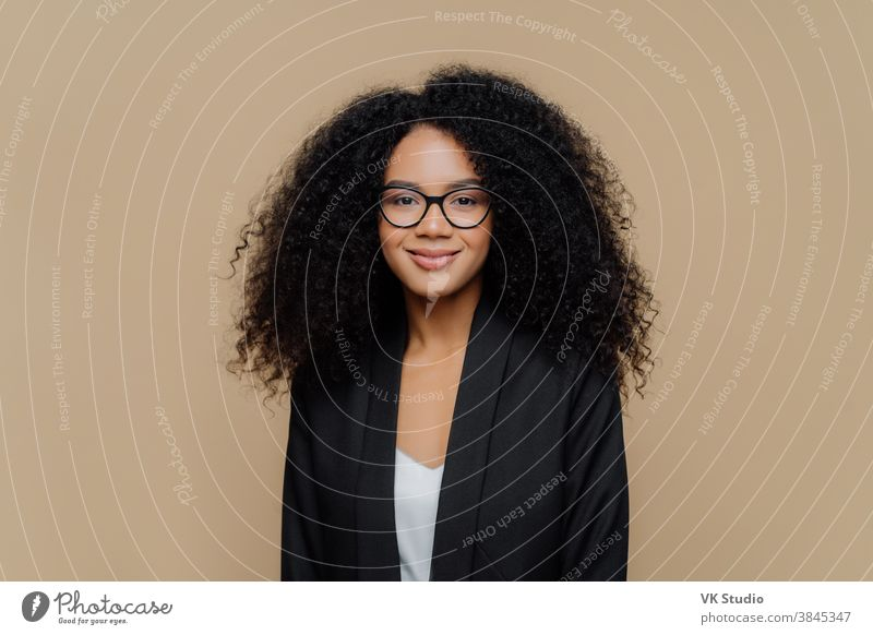 Portrait of beautiful Afro American woman with crisp hair, dressed in elegant black jacket, transparent glasses, looks directly at camera with gentle smile wears optical glasses isolated on brown wall