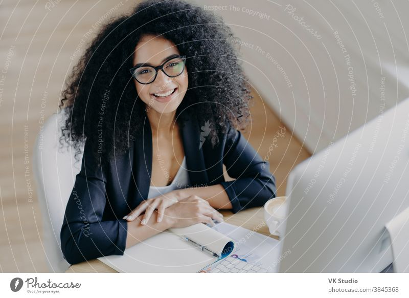 Top view of glad African American businesswoman smiles pleasantly, notes information, makes notes, wears transparent glasses, formal clothes, computer monitor in front, sits at desktop alone