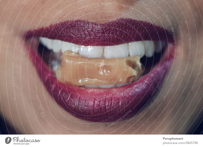Close-up of woman mouth biting caramel candy closeup female food lips red girl person tasty teeth young bite sexy pink caucasian eating face makeup sugar