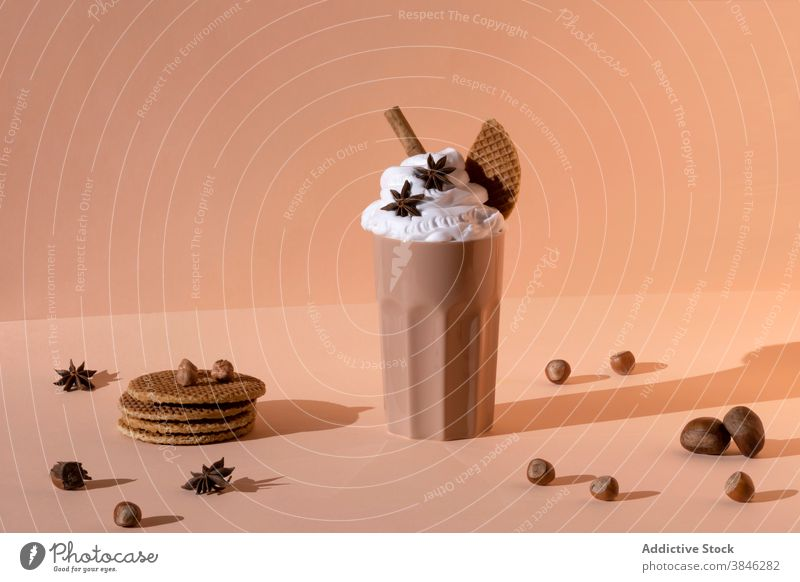 Delicious chocolate milkshake in studio cocktail sweet delicious whipped cream spicy beverage glass tasty drink sugar star anise cinnamon stick table gourmet