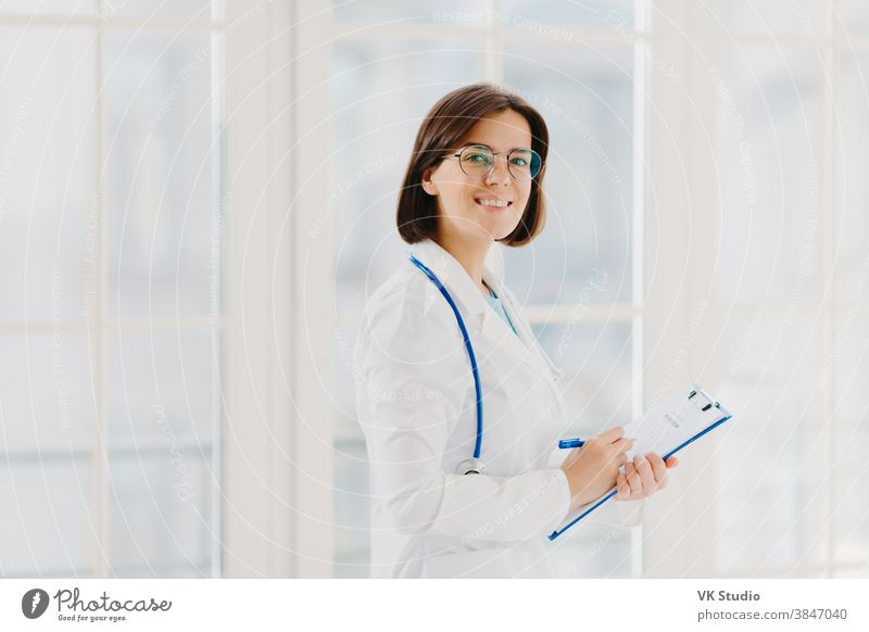 Horizontal shot of female doctor fills up medical form at clipboard, stands indoor, wears round glasses, white gown and stethoscope. General practitioner writes down notes, consults patients