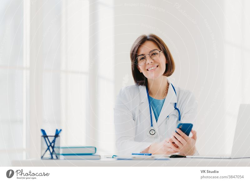 Horizontal view of smiling professional doctor works in clinic, poses at modern hospital office with electronic gadgets, sends text messages on cellphone being at work. Health care, technology concept