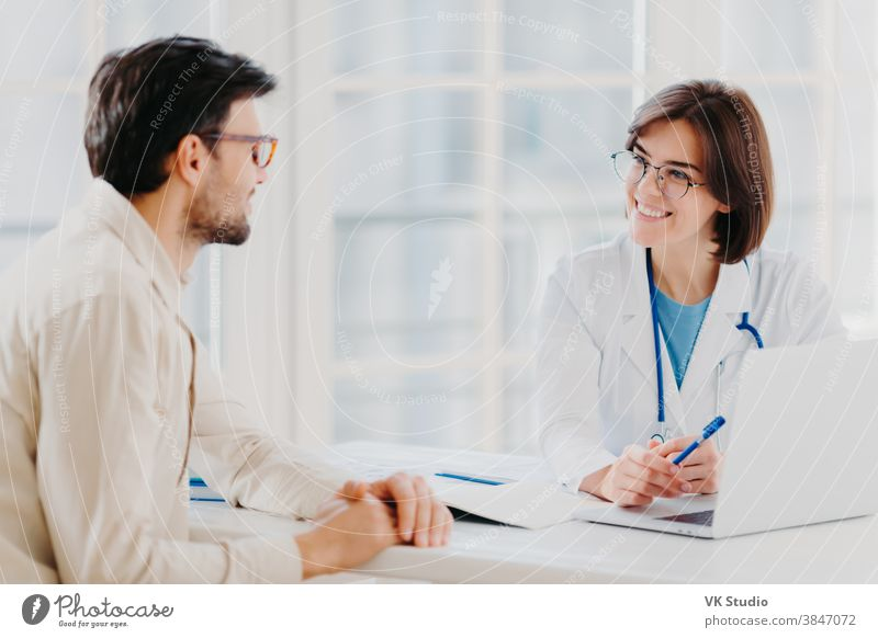 Skilled professional female general practitionist explains diagnosis and consults patient, demonstrates information in laptop, pose in clinical office, discuss scan results in diagnostic center