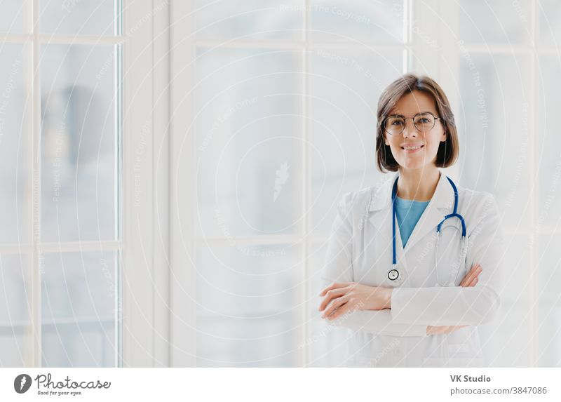 Self confident professional doctor stands with arms crossed, wears white medical gown with stethoscope, thinks about work positively, poses against big window. Healthcare and occupation concept