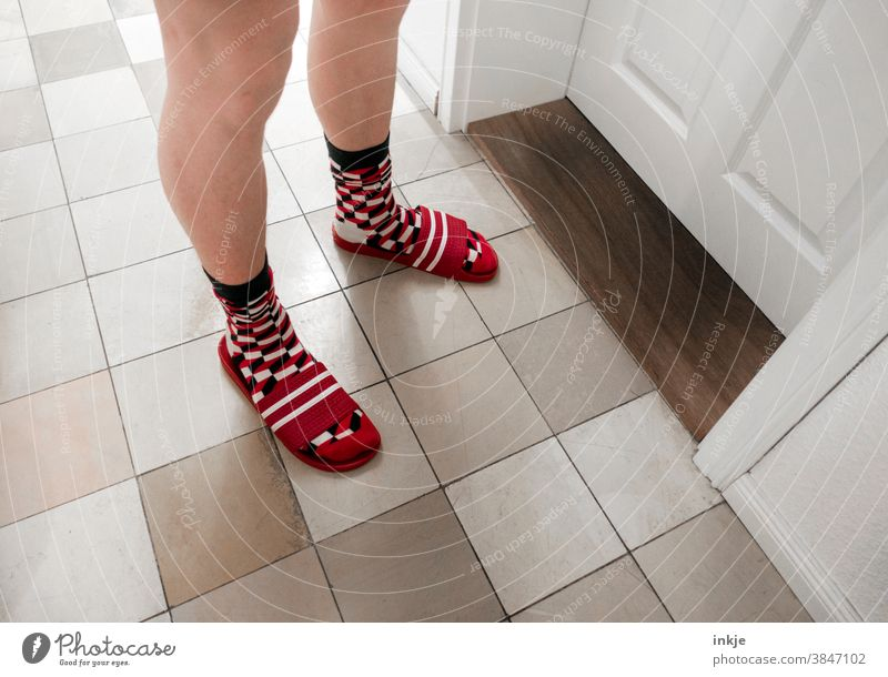 Pale legs stand before a closed door. Checked socks in striped flip-flops. Colour photo Interior shot Legs Boy (child) young man Stand Day Room Hallway