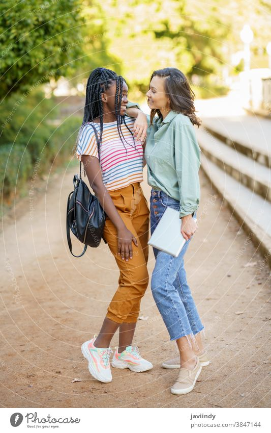 Two multiethnic women posing together with colorful casual clothing woman friend tablet digital female girl young lifestyle urban beautiful device outside lady
