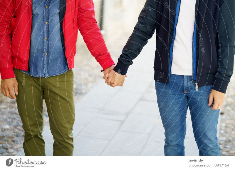 Gay couple holding hands in the street. gay men male love outdoors homosexual lgbt lgbtq relationship lovers boyfriend people adult outside urban background
