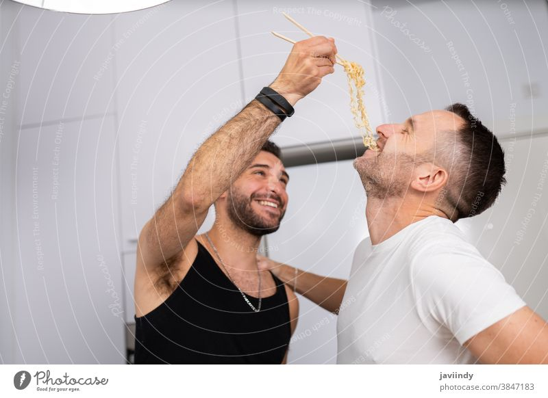 Man feeding pasta to his boyfriend in a fun way gay couple men homosexual spaghetti food cooking kitchen lgbt love lgbtq male relationship lovers people 30s