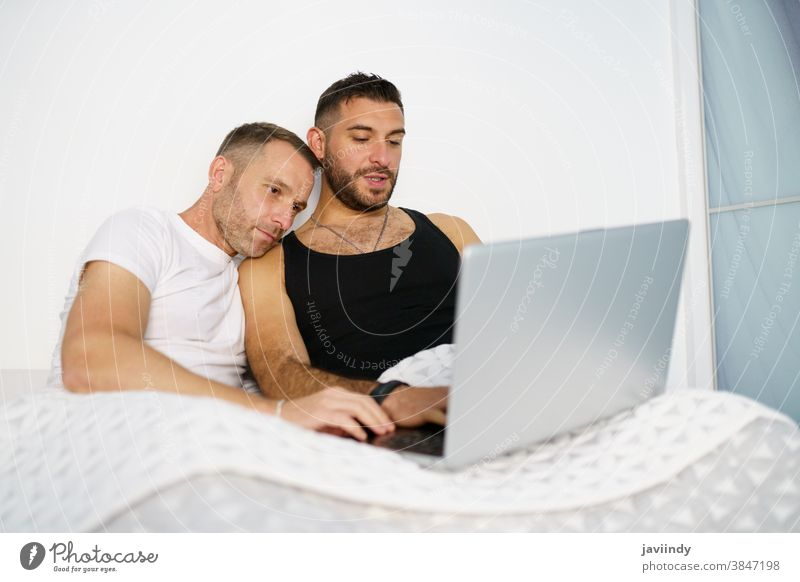 Gay couple consulting something on their laptop while lying on the bed. gay men homosexual lgbt lgbtq male relationship boyfriend people 30s togetherness man