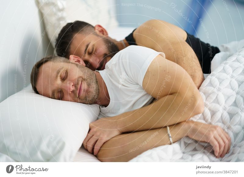 Gay couple sleeping in each other's arms. gay men homosexual bed lgbt love lgbtq male relationship lovers boyfriend people 30s togetherness caucasian hispanic