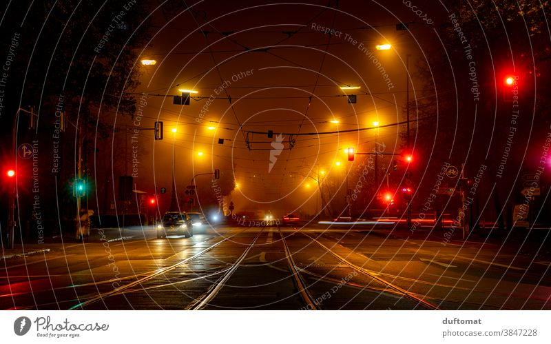 Long-term exposure of an intersection at night Traffic light out Town Light blurred background Evening Night life Street cross trees Car Fog Mobility
