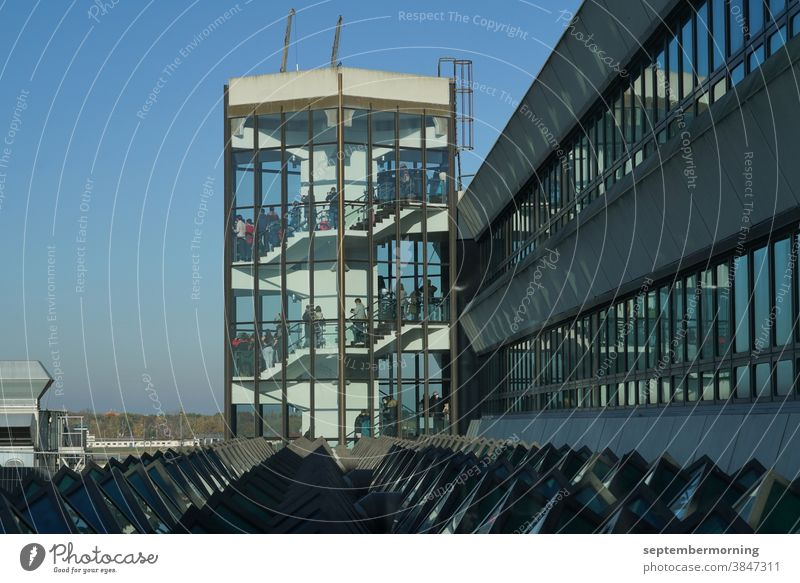 Tower made of glass, internal stairs, many people on the steps, light blue sky, building complex connects to the tower, steel construction Tower transparent