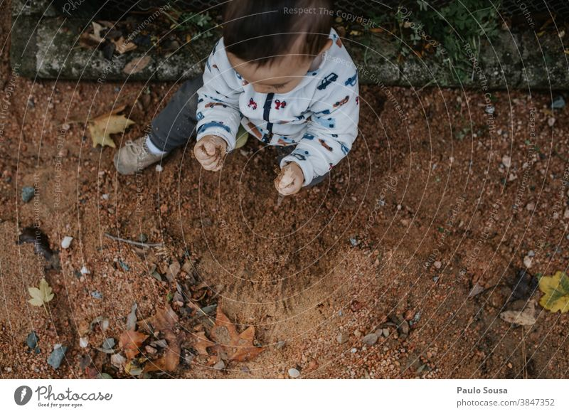 Toddler playing with sand at the park Authentic Sand flooring Child Children's game childhood Nature Curiosity Happiness Human being Leisure and hobbies
