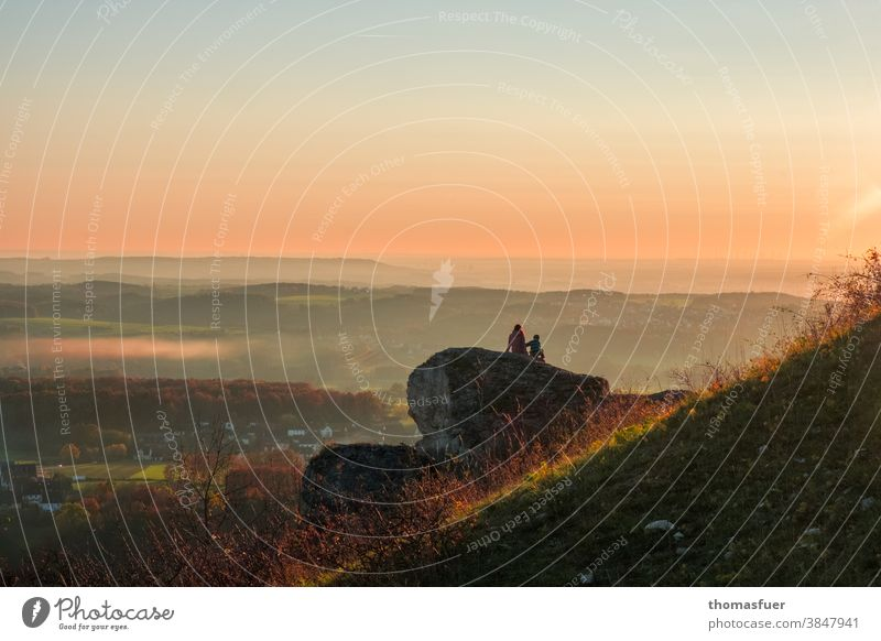 Couple sitting on a rock looks into the distance and watches the sunset Beautiful weather Sunday Autumn Sky colors mountain Mother Child Sunset Nature Landscape