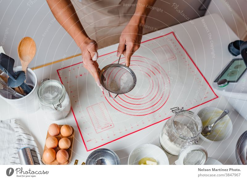 Hands of a man sifting flour by sieve in the table. Eggs bakery desserts butter salt food cooking home home made healthy copy space containers business