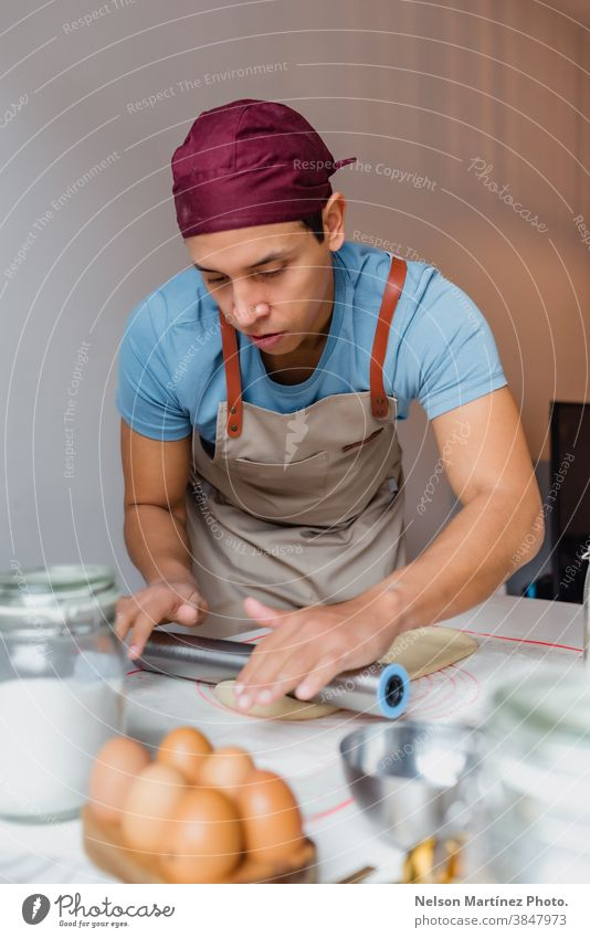 Man kneading dough over a white table. adult man indoor cooking flour chef restaurant employment food Eggs bakery desserts butter salt home home made healthy