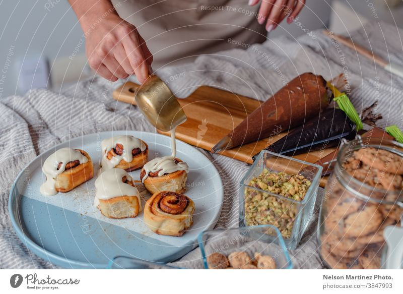 Woman preparing and decorating cinnamon rolls. adult indoor cooking dough flour chef restaurant employment food Eggs bakery desserts butter salt home home made