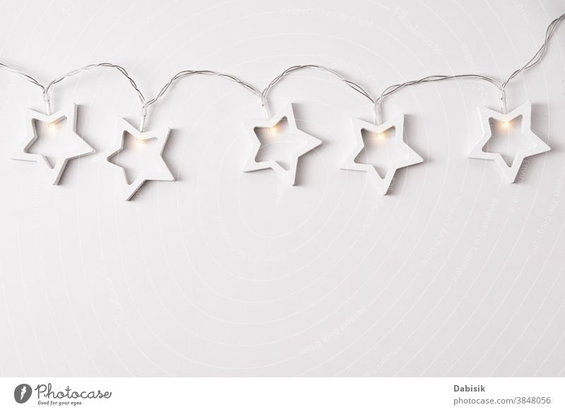 Christmas composition. Garland made of wooden stars on white background. Flat lay christmas decor garland wall shape ornament table holiday xmas isolated view