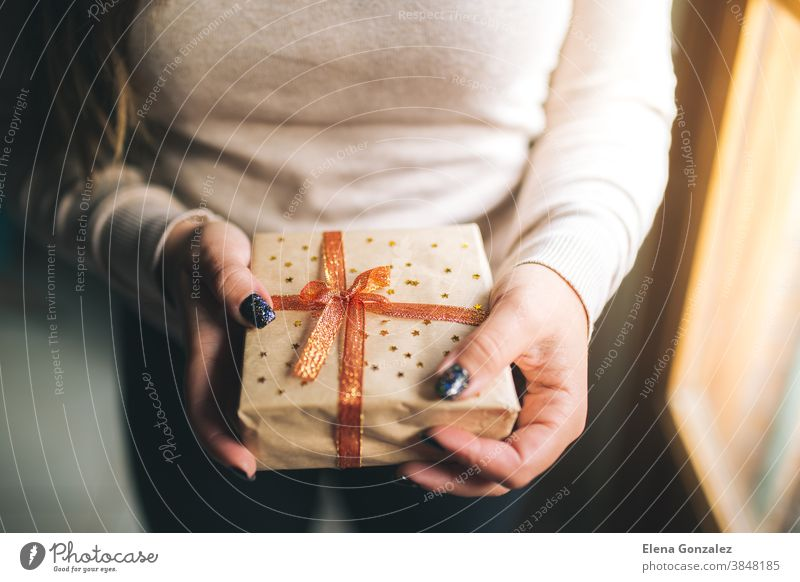 Young women with glitter nails holding Christmas present box and showing it in camera. Hands hold new year gift box. decorated with craft paper, red and golden ribbon and stars. Family gift concept.