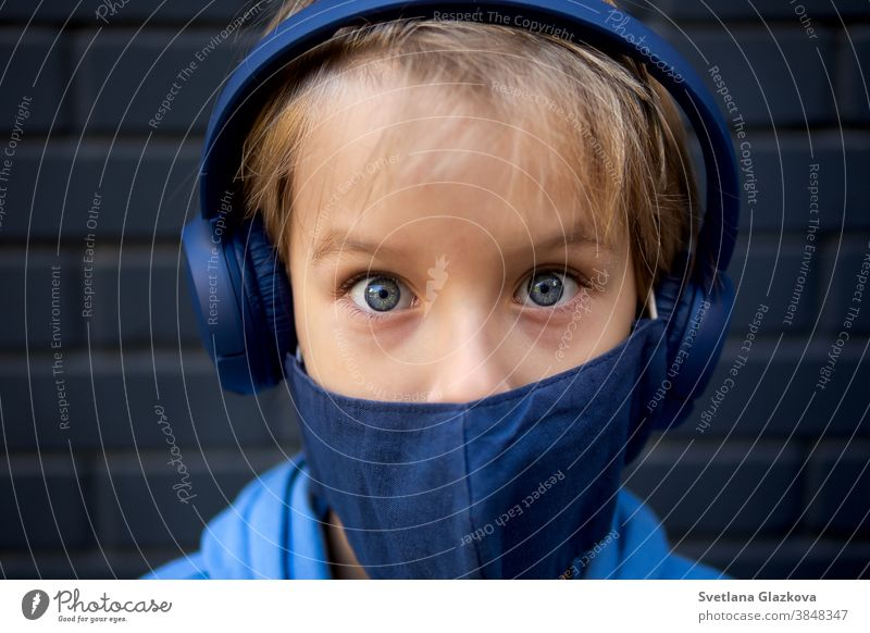Close-up face portrait of a blonde caucasian boy. Looks at the camera. Dressed in a protective medical mask and blue headphones eyes close-up funny kid child