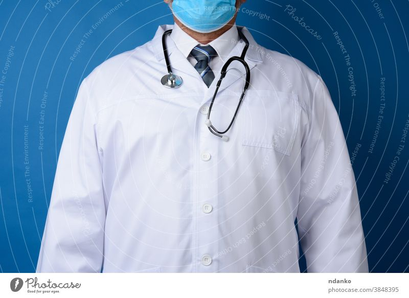 doctor in a white coat stands on a blue background adult cardiologist care caucasian clinic expertise front health healthcare hospital illness indoors job male