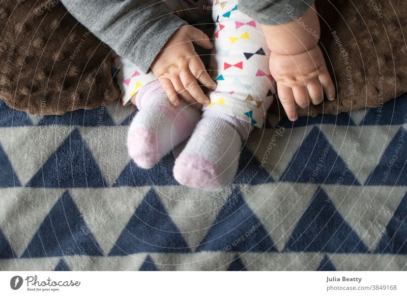 Baby reaching for feet, dimpled baby hands, triangle print blanket and pants child foot newborn love small toes care human kid childhood little family barefoot