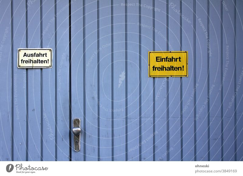 """Garage door with warning signs """"Keep exit clear"""" """"Keep entrance clear"""". Highway ramp (entrance) Signs and labeling Signage Warning sign Characters"""
