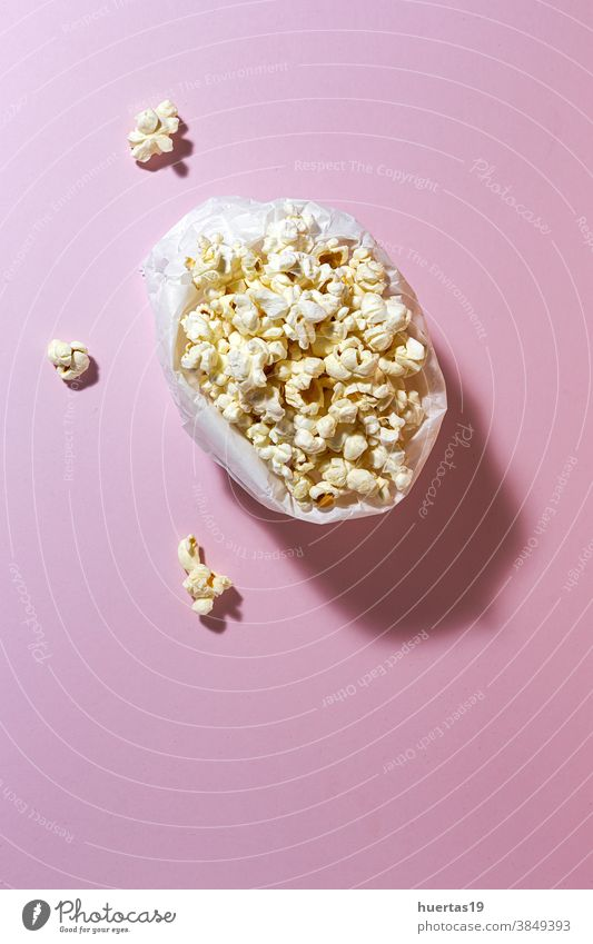Homemade popcorn on on colorful backgrounds snack entertainment food delicious tasty salty salted fresh fluffy classic sweet paper modern takeaway design