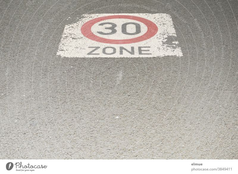 "A speed limit sign ""Zone 30"" is painted on the asphalt road / traffic-calmed zone / drive slowly / speed limit 30 Road sign Speed limit 30 mph zone at 30 kph"