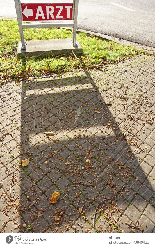 """Red sign """"ARZT"""" casts a shadow on the footpath / orientation / signpost Doctor Signage Arrow Street Footpath Signs and labeling Lanes & trails Shadow"""