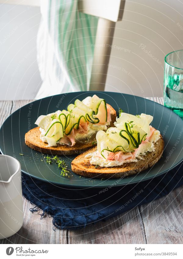 Rye bread toasts with cheese, ham, cucumber sandwich food vegetable fresh slice rye breakfast set wooden black dish delicious lunch brunch meal trendy styling