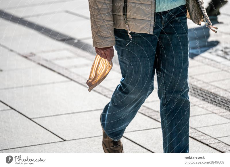 Person Holding Mask in Hand Outside new normal mask hand medium shot street walking day sunny spring unrecognizable people restriction lockdown jeans holding