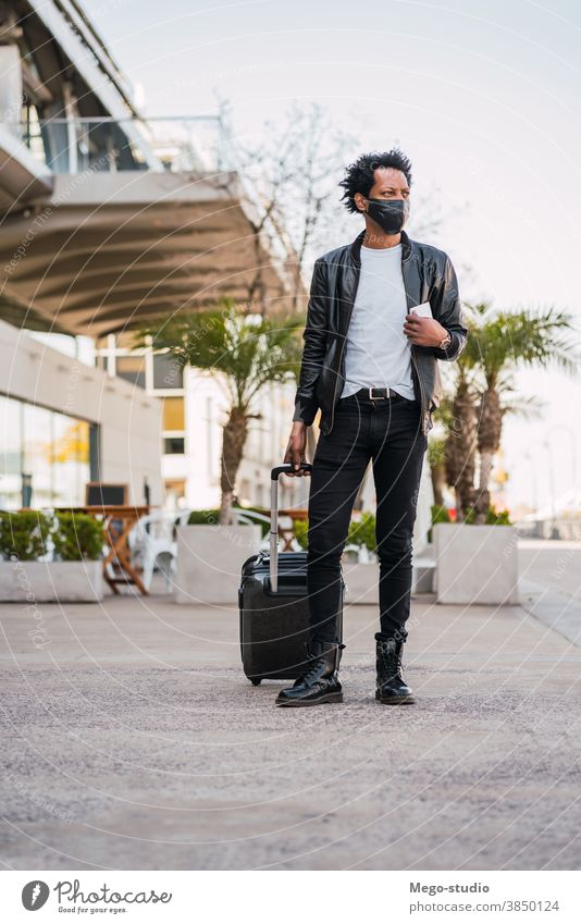 Tourist man carrying suitcase while walking outdoors. afro tourist traveler destination concept travelling holiday joy enjoy adventure traveller vacations