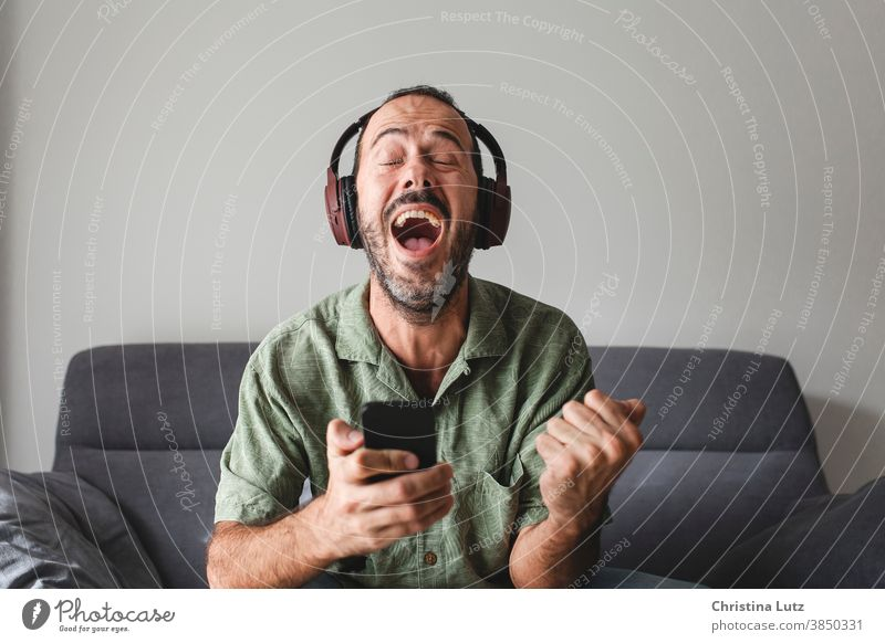 man sitting on sofa with mobile phone and headphones, shouting for joy while winning sports betting scream for joy smartphone results enthusiastic closed eyes