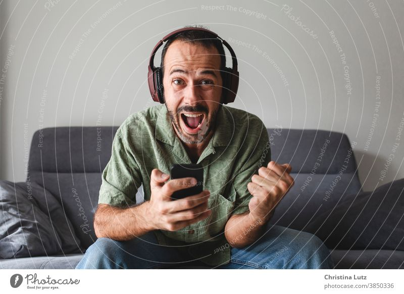 man sitting on sofa and shouting for joy, while winning sports betting with mobile phone scream for joy clenched fist yelling headphones enthusiastic results