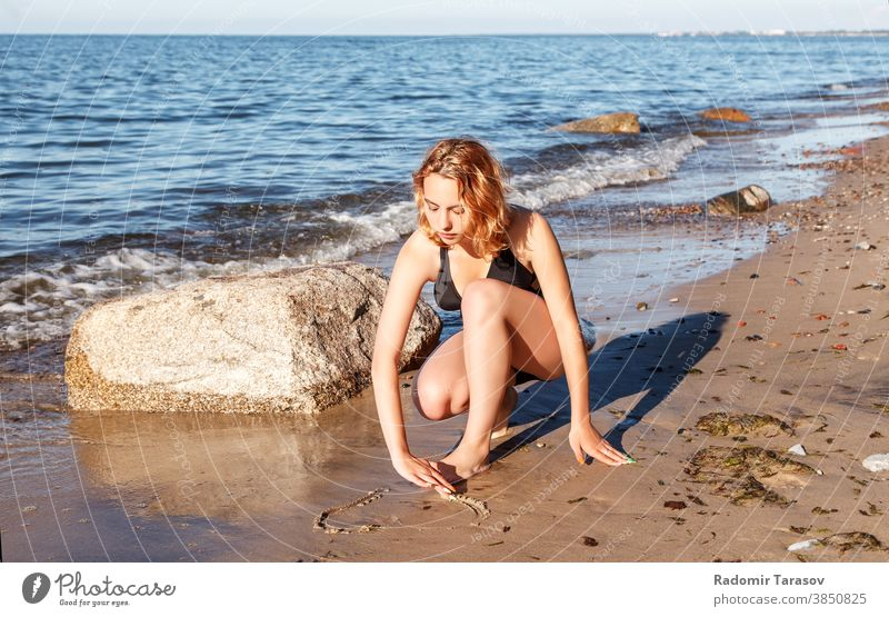 young girl in a swimsuit draws with her finger on the sand by the seashore beauty happy beautiful drawing sunny female water coast ocean holiday wave summer