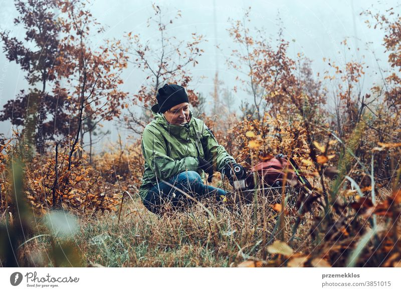 Woman with backpack having break during autumn trip drinking a hot drink from thermos flask on autumn cold day outdoors destination hiking holiday vacation