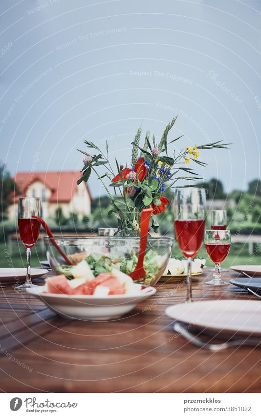 Dinner in an apple orchard on wooden table with salads and wine decorated with flowers home feast picnic food summer barbecue dinner gathering lifestyle meal