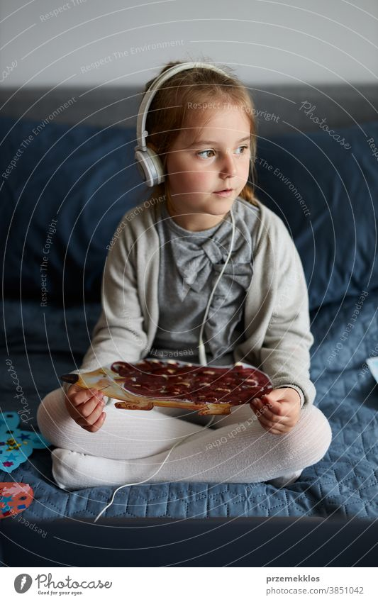 Little girl preschooler learning online showing her works drawings done at home child watching listening educational puzzle bed internet small room game movie