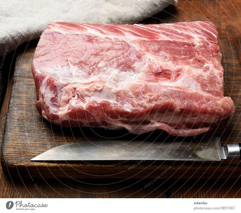 raw pork tenderloin on a wooden cutting board meat napkin nutrition piece portion preparation protein red sirloin butcher chop closeup cuisine dinner fat filet