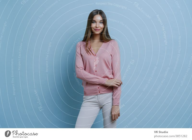 Fashionable brunette Caucasian woman dressed in pink jumper and white trousers, going to work, applies makeup, smiles pleasantly, isolated on blue background. People, style, lifestyle concept