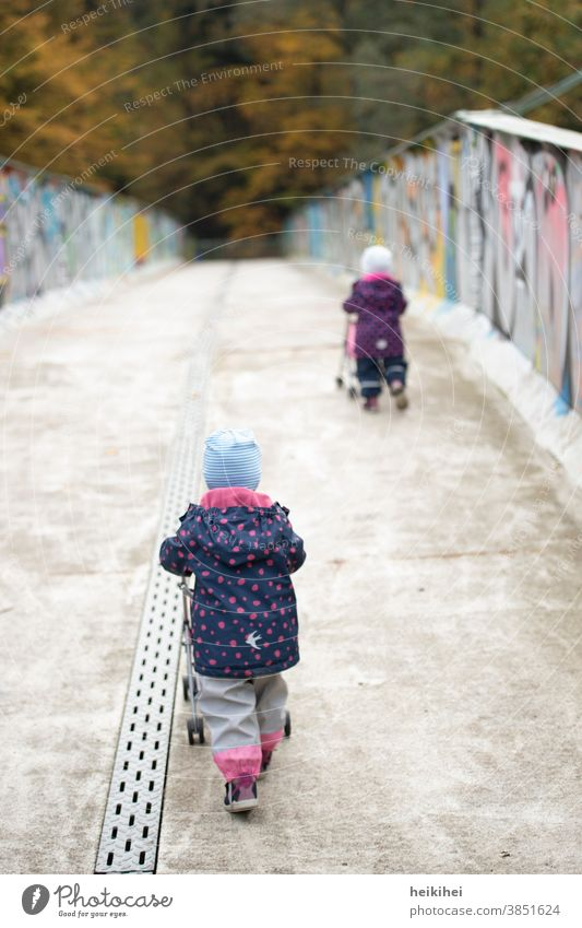 two small children with prams on the way to the playground Girl Small Child Park Family Forest Autumn people Bridge Town urban Push Going Baby carriage winter
