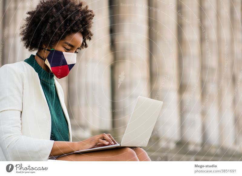 Business woman using her laptop outdoors. young afro business urban street success device face mask information protect protective mask covid-19 connection