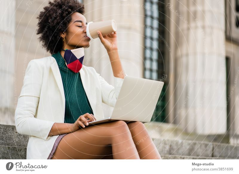 Business woman using her laptop outdoors young afro business urban street success device corporate information coffee face mask protective mask connection