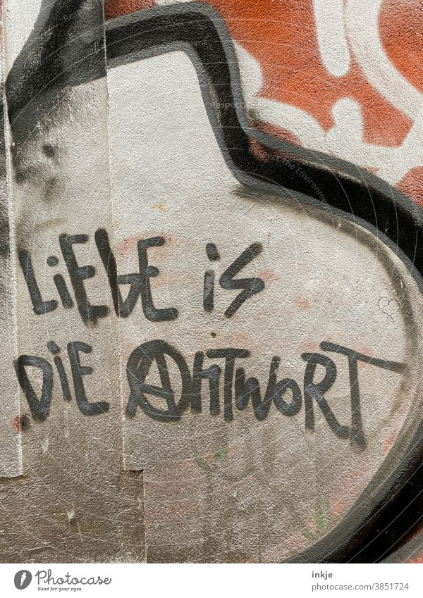 German graffiti on the facade Colour photo Exterior shot Graffiti Love saying Answer Meaning Facade writing urban meaning of life antifa policy harmony